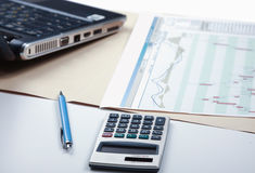 Калькулятор, ручка, компьтер-книжка, документ лежа на столе Стоковые Фото