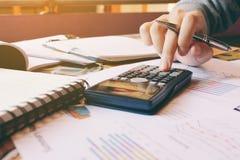 Калькулятор с женщиной руки высчитывает о цене в домашнем офисе Стоковое Изображение RF