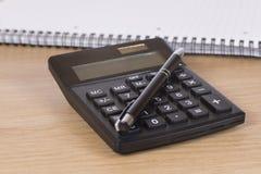 Калькулятор с ручкой на столе Стоковая Фотография