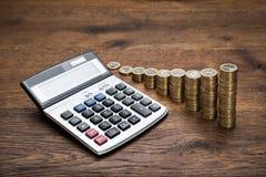 Калькулятор с стогом монеток Стоковые Фотографии RF