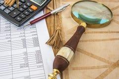 Калькулятор, лупа и ручка, лежа на открытой кожаной папке Стоковая Фотография