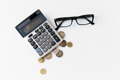 Калькулятор, eyeglasses и монетки евро на таблице Стоковая Фотография RF