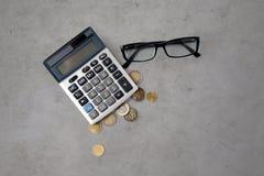Калькулятор, eyeglasses и монетки евро на таблице Стоковая Фотография