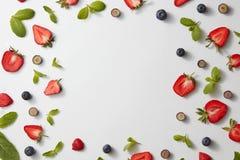 Квадратная рамка сделанная из листьев, клубник и голубик мяты на серой предпосылке Плоское положение Стоковые Изображения