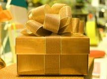 Квадратная сияющая подарочная коробка золота с смычком ленты золота яркого блеска, запачканной предпосылкой Стоковые Фотографии RF