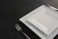 Квадратные плиты и столовый прибор установили на таблицу Стоковые Фото