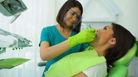 Квалифицированные зубы женщины дантиста рассматривая, регулярн проверка в современной клинике сток-видео