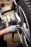 Квалифицированный молодой механик изменяя автошину поднятого автомобиля Отремонтируйте мастерскую стоковые изображения