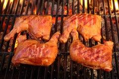 4 квартала ноги цыпленка зажаренного в духовке на горячем гриле BBQ пламенеющем Стоковое Изображение RF