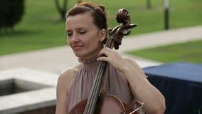 квартет игры аппаратур детей музыкальный Девушка играя виолончель в квартете скрипачей конец вверх сток-видео