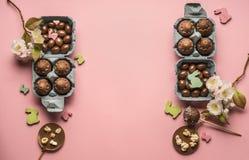Квартира пасхи кладет украшения яичек шоколада различные, деревянные кроликов и поздравительную открытку птиц, на розовую предпос Стоковое Фото