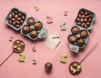 Квартира пасхи кладет украшения яичек шоколада различные, деревянные кроликов и поздравительную открытку птиц, на розовую предпос Стоковые Фото