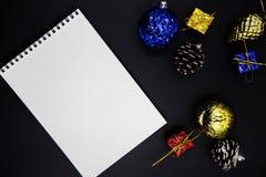 Квартира тетради оформления и белой бумаги рождества кладет на черную предпосылку Модель-макет рождества или Нового Года стоковые изображения