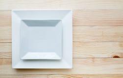 Квадратные белые плиты над деревянным столом Стоковая Фотография