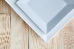 Квадратные белые плиты над деревянным столом Стоковые Изображения
