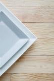 Квадратные белые плиты над деревянным столом Стоковое Изображение RF