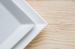 Квадратные белые плиты над деревянным столом Стоковое Фото