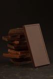 Квадратные форменные части шоколада на темной предпосылке Стоковое Фото