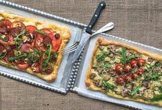 2 квадратных пиццы с свежими arugula и вишн-томатами на silv Стоковое фото RF