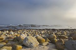 Кейптаун приносит волны к пляжу, камни различных размеров Стоковое фото RF