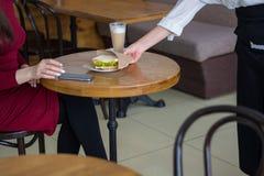 Кельнер дает девушке сандвич Девушка с мобильным телефоном внутри Стоковое фото RF