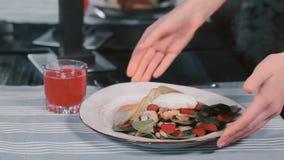 Кельнер кладет плиту с салатом на таблицу видеоматериал