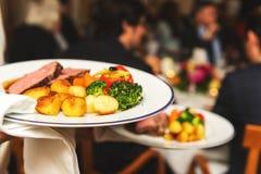 Кельнер нося 2 плиты с мясным блюдом Стоковое Изображение RF