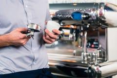 Кельнер подготавливая эспрессо на автоматической машине кофе Стоковое Изображение RF