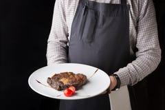 Кельнер предлагая очень вкусное блюдо ресторана Стоковые Фотографии RF