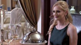 Кельнер раскрывает крышку tableware - cloche показывая блюдо перед белокурой девушкой Точная обедая концепция ресторана сток-видео