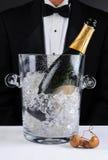 Кельнер стоя за ведром Шампань стоковые изображения