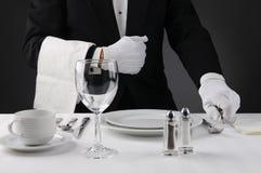 Кельнер устанавливая официально обеденный стол Стоковое Изображение