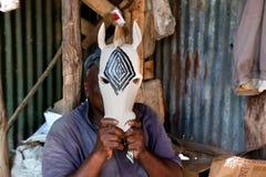 КЕНИЯ, АФРИКА - 10-ОЕ ДЕКАБРЯ: Человек высекая диаграммы в древесине. Стоковое Изображение RF