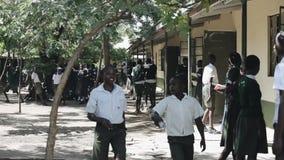 КЕНИЯ, KISUMU - 20-ОЕ МАЯ 2017: Африканские дети в форме и учителях тратя время вне близко школы сток-видео