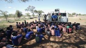 КЕНИЯ, KISUMU - 20-ОЕ МАЯ 2017: Африканские дети сидя на том основании и слушают к кавказским людям и женщинам сток-видео