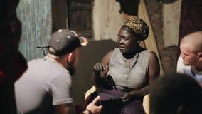 КЕНИЯ, KISUMU - 20-ОЕ МАЯ 2017: Африканский сидеть женщины внешний и разговаривать с кавказским человеком в солнечном летнем дне видеоматериал