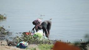 КЕНИЯ, KISUMU - 20-ОЕ МАЯ 2017: 2 африканских женщины оставаясь на береге озера и моя блюд совместно сток-видео