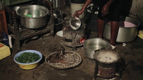 КЕНИЯ, KISUMU - 20-ОЕ МАЯ 2017: Взгляд конца-вверх молодой африканской женщины подготавливая обедающий, чиреи мочит на горящих уг сток-видео