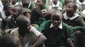 КЕНИЯ, KISUMU - 20-ОЕ МАЯ 2017: группа в составе африканские дети в зеленой форме сидя на земле, усмехающся, говоря акции видеоматериалы