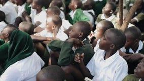 КЕНИЯ, KISUMU - 20-ОЕ МАЯ 2017: Группа в составе африканские дети в зеленой форме сидя на земном снаружи, около школы видеоматериал