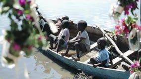 КЕНИЯ, KISUMU - 20-ОЕ МАЯ 2017: Группа в составе африканские дети сидя в шлюпке и смотря на воде моря видеоматериал