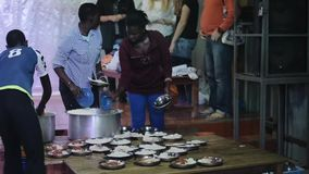 КЕНИЯ, KISUMU - 20-ОЕ МАЯ 2017: Группа в составе африканские подростки кладя подъем в плиты, подготавливая обедающий совместно видеоматериал