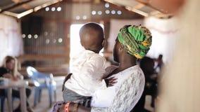 КЕНИЯ, KISUMU - 20-ОЕ МАЯ 2017: Дом африканской семьи Молодая женщина держит ее маленького сына в ее руках акции видеоматериалы