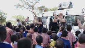 КЕНИЯ, KISUMU - 20-ОЕ МАЯ 2017: Кавказец вызывается добровольцем танцы с африканскими зрачками, детьми вне школы сток-видео