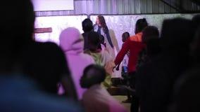 КЕНИЯ, KISUMU - 20-ОЕ МАЯ 2017: Кавказская женщина на танцах этапа, движения показа к большой группе в составе африканские дети видеоматериал
