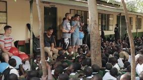 КЕНИЯ, KISUMU - 20-ОЕ МАЯ 2017: Кавказские люди стоя и говоря в африканской школе к группе в составе дети акции видеоматериалы