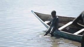 КЕНИЯ, KISUMU - 20-ОЕ МАЯ 2017: Красивый африканский мальчик сидит в шлюпке на береге озера и отбрасывает его акции видеоматериалы
