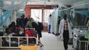 КЕНИЯ, KISUMU - 20-ОЕ МАЯ 2017: Местная больница в Африке Кавказские люди сидя на кроватях и разговаривая с африканскими людьми видеоматериал