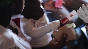 КЕНИЯ, KISUMU - 20-ОЕ МАЯ 2017: Молодая африканская мать с сыном принимает медицинские подготовки от доктора акции видеоматериалы