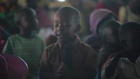 КЕНИЯ, KISUMU - 20-ОЕ МАЯ 2017: Портрет счастливого африканского мальчика сидя внутрь при группа в составе дети и танцы, усмехаяс сток-видео